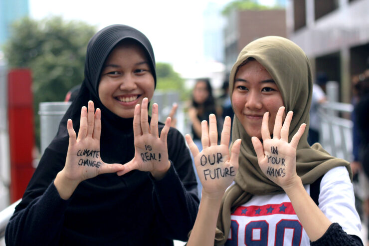 """Two young women with """"Climate Change is Real! Our future in your hands"""" written on their palms"""