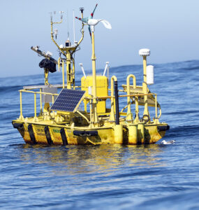 A yellow buoy with multiple sensors floats in open sea